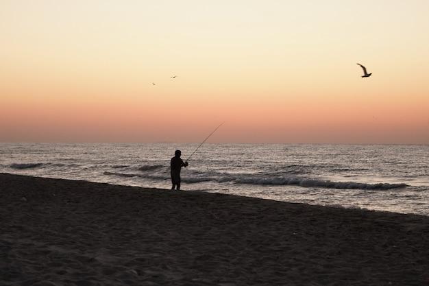 Il pescatore pesca i pesci dalla riva al tramonto