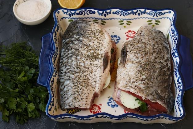 Il pesce crudo ripieno di cipolle ed erbe si trova in un piatto di ceramica. sul tavolo, sale, limone, aneto e prezzemolo