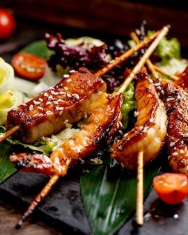 Il pesce e i gamberi fritti sui bastoni sono serviti con i pomodori e le cipolle della lattuga