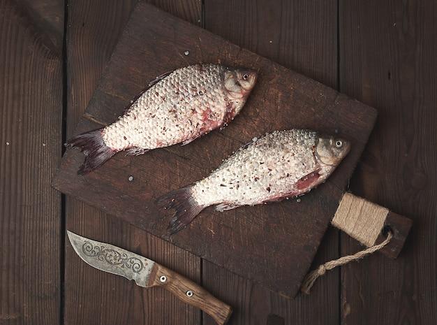 Il pesce fresco di crucian si trova su un tagliere di legno marrone