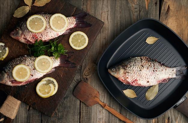 Il pesce fresco nelle scale crucian su un vecchio tagliere di legno marrone, alimento condito con le spezie