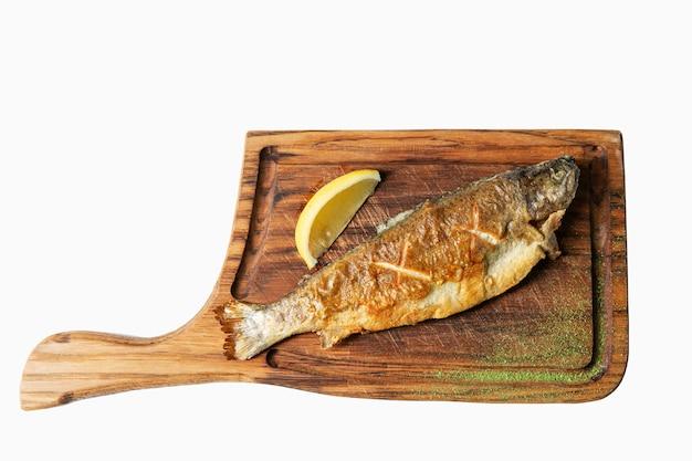 Il pesce fritto con il limone è servito su un tagliere di legno. isolato su bianco