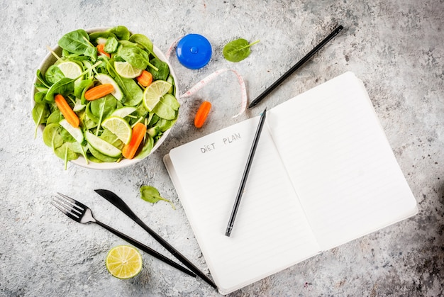 Il peso del piano di dieta perde l'insalata della verdura fresca di concetto con la tavola della pietra del padgrey della nota del coltello della forcella