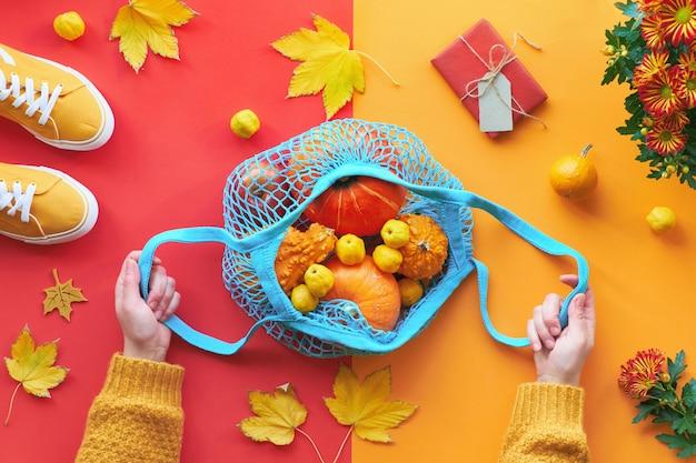 Il piano autunnale si stende sul fondo di carta rosso e arancio spaccato zucche arancioni in borsa a rete blu o borsa a stringhe tenuta a mano in maglione giallo e sneaker in tela gialla.