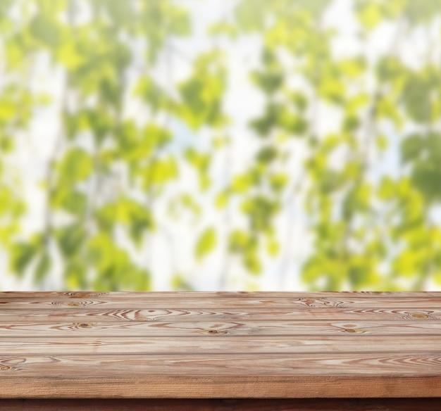 Il piano d'appoggio di legno su fondo astratto della sfuocatura con i rami della betulla - può essere usato per esposizione o il montaggio i vostri prodotti.