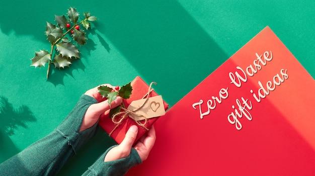 Il piano panoramico creativo giaceva su carta verde e rossa con lunghe ombre. contenitore di regalo avvolto holdi femminile delle mani decorato con agrifoglio. natale ecologico, testo