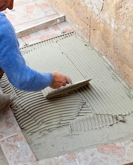 Il piastrellista lavora con la pavimentazione.