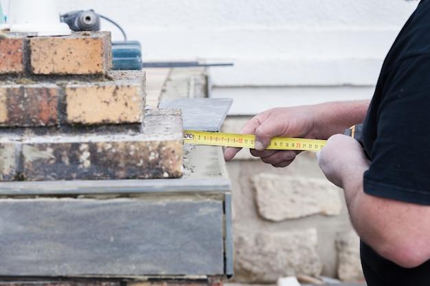 Il piastrellista misura e mette i segni per tagliare e posare una piastrella