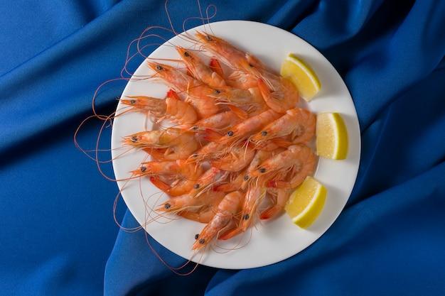 Il piatto bianco con i gamberetti saporiti con il limone è servito sul blu. vista dall'alto