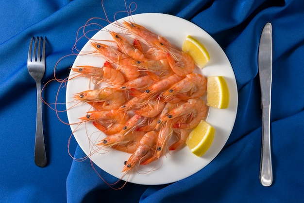 Il piatto bianco con i gamberi saporiti con il limone è servito sull'azzurro con la forchetta e la lama. vista dall'alto