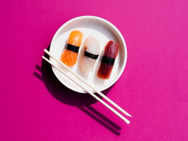 Il piatto bianco dei sushi con il taglio attacca su un fondo rosa