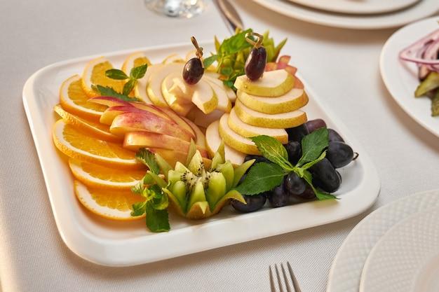 Il piatto con frutta affettata sta su una tavola servita in un ristorante