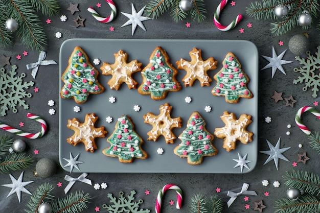 Il piatto dei biscotti di natale ha modellato come alberi di natale e fiocchi di neve sul piatto grigio su buio decorato
