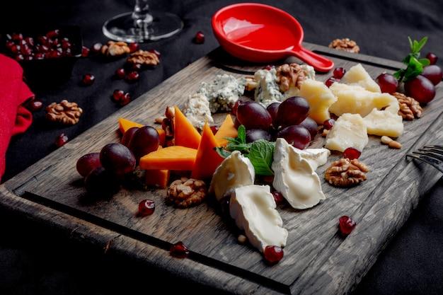 Il piatto di formaggi è servito con l'uva, il miele e le noci su un fondo di legno. vari tipi di formaggio