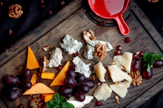 Il piatto di formaggi è servito con l'uva, il miele e le noci su una tavola di legno. vari tipi di formaggio