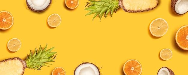 Il piatto di frutta tropicale giaceva con ananas, arance, limone e cocco su uno sfondo pastello.