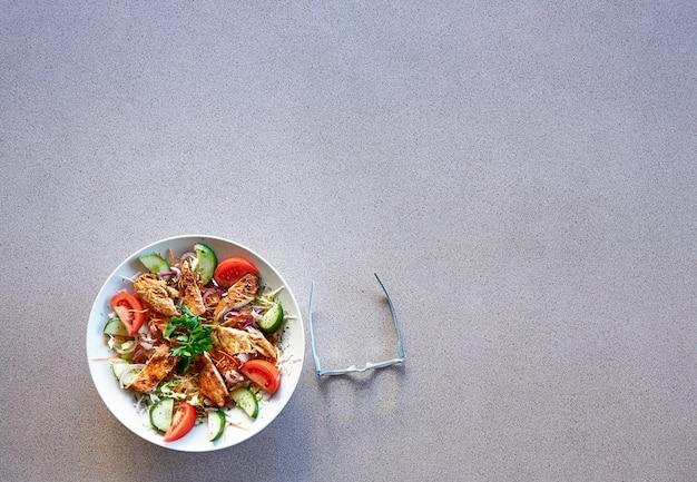 Il piatto di insalata di pollo e gli occhiali su darken alleggeriscono il fondo strutturato