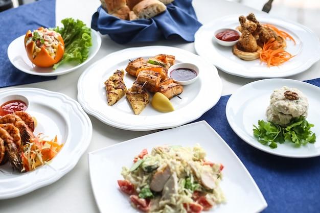 Il piatto mette l'insalata di tonno di caesar i gamberi la vista laterale delle coscie di pollo