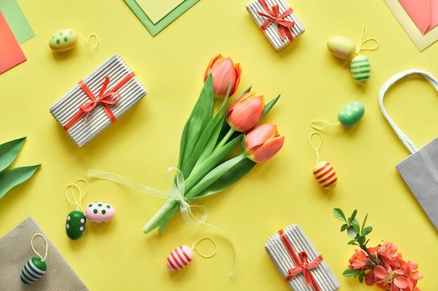 Il piatto pasquale giaceva su carta gialla. mazzo di tulipani, scatole regalo, uova decorative e sacchetti di carta, disposizione geometrica diagonale.