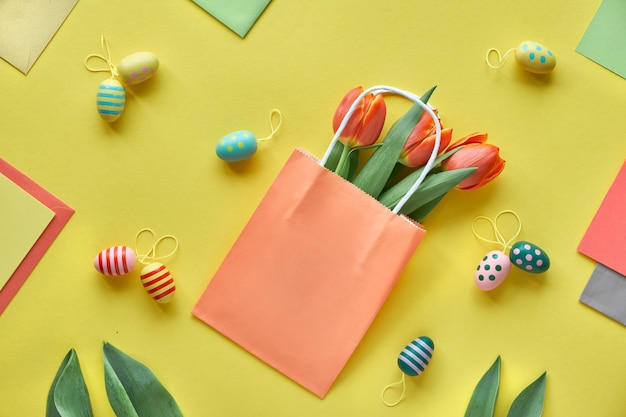 Il piatto pasquale giaceva su carta gialla. mazzo di tulipani, scatole regalo, uova decorative e sacchetti di carta, disposizione geometrica