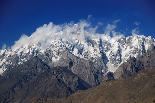 Il picco della montagna di ultar sar dietro le nuvole. batura muztagh, gamma karakoram. pakistan.