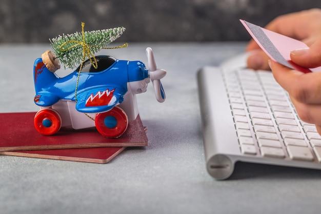 Il piccolo aeroplano con l'albero di natale, i passaporti, la tastiera, la carta di credito sulla mano grigia della donna sta scrivendo
