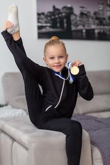 Il piccolo atleta con una medaglia d'oro mette in mostra il suo sportivo dane