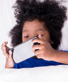 Il piccolo bambino africano sta giocando con lo smartphone sul letto