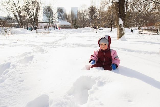 Il piccolo bambino è caduto nella neve e si siede