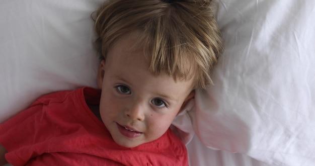 Il piccolo bambino giace a letto. il bello ragazzo si trova in vista superiore del bambino felice e allegro dei vestiti pastelli bianchi
