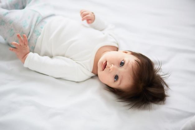 Il piccolo bambino giace sul letto