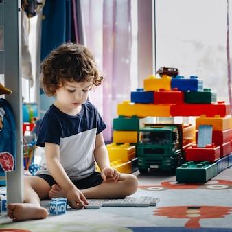 Il piccolo bambino gioca a domino nella sua stanza sul pavimento
