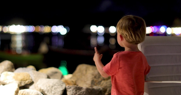 Il piccolo bambino mostra le luci ha riflesso l'acqua