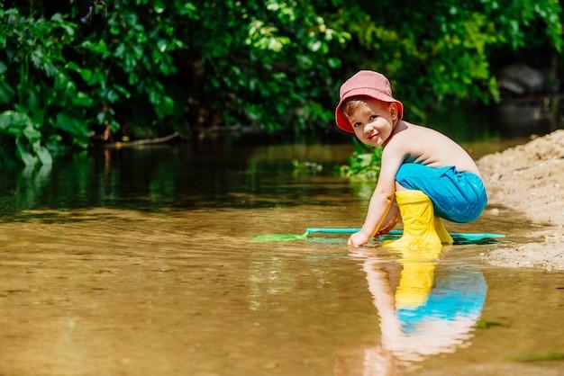 Il piccolo bambino pesca pesci e rane nel fiume