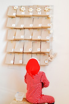 Il piccolo bambino sta aspettando sullo sgabello l'inizio del calendario dell'avvento per natale.