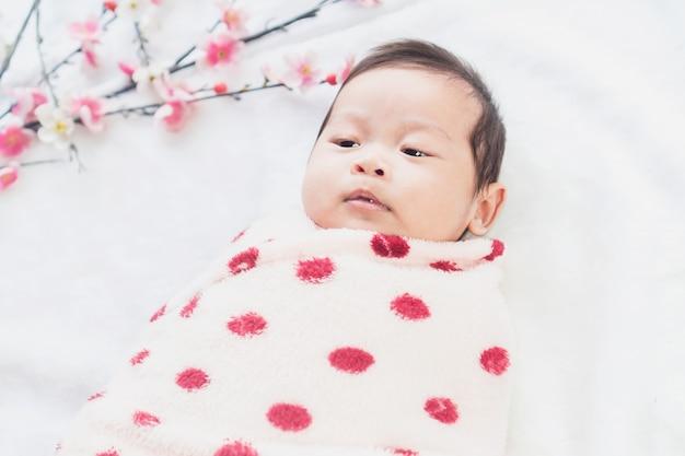 Il piccolo bambino sveglio si trova su un panno bianco ed è avvolto in trapunta