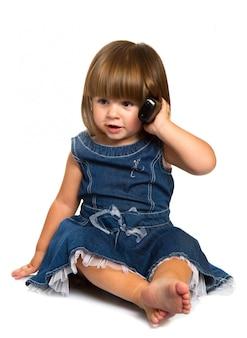 Il piccolo bambino sveglio sta parlando sul telefono cellulare, isolato sopra bianco