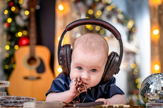 Il piccolo bambino sveglio sta trovandosi sulla sua pancia con le cuffie e sta ascoltando la musica.