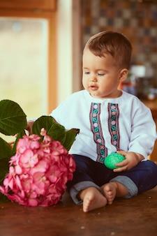 Il piccolo bambino tiene un uovo verde e si siede vicino al fiore