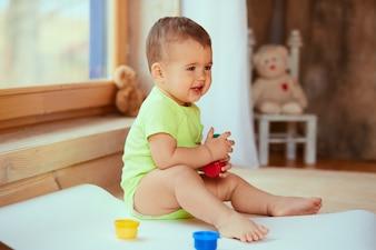 Il piccolo bambino tiene una scatola con le vernici