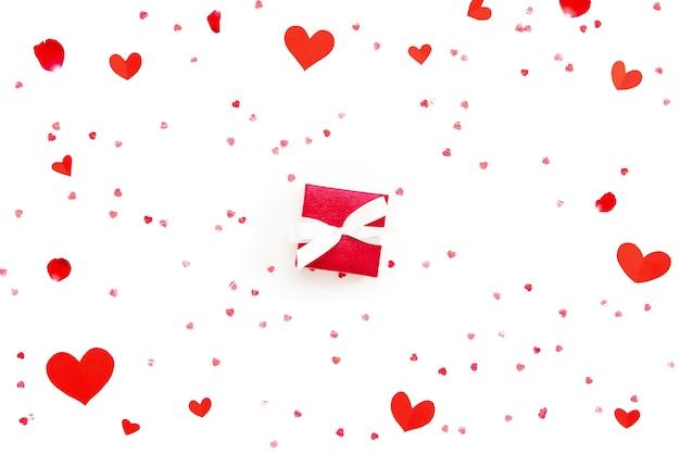 Il piccolo contenitore di regalo rosso di san valentino con cuore modella sul fondo del libro bianco