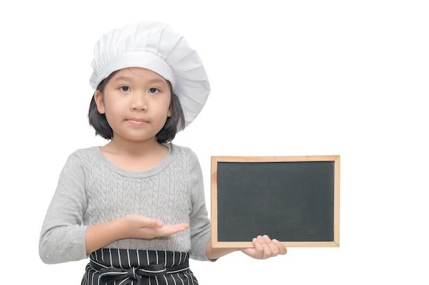 Il piccolo cuoco unico asiatico della ragazza in uniforme giudica la lavagna della tenuta per dentro manda il testo o il menu, isolato su bianco