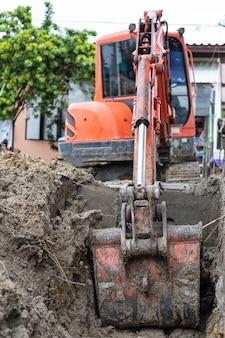Il piccolo escavatore a cucchiaia rovescia sta scavando un buco sul cantiere