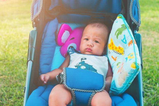 Il piccolo neonato asiatico di sei mesi sveglio si siede sul trasporto del passeggiatore in parco