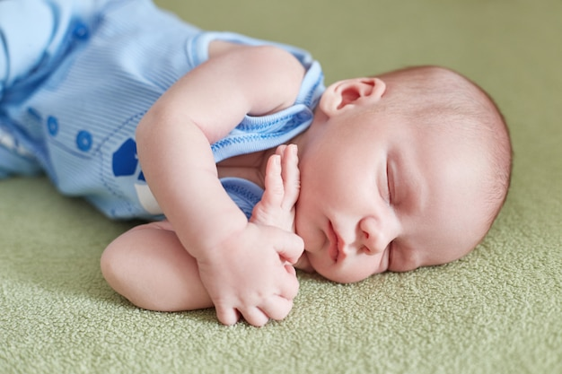 Il piccolo neonato è sdraiato sul divano. bambino
