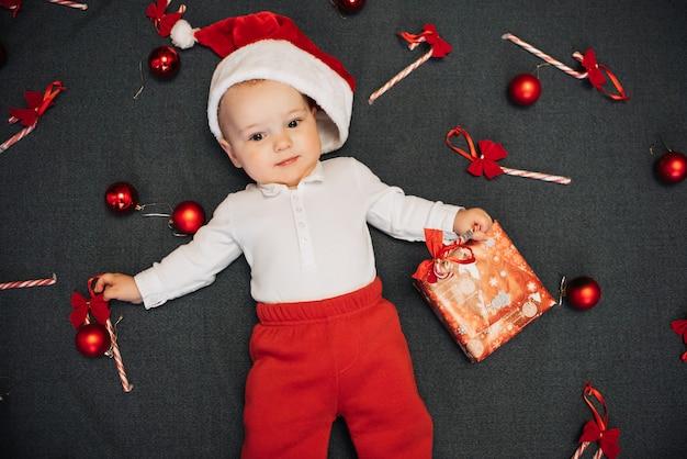 Il piccolo neonato in cappello della santa sta trovandosi fra le caramelle, le sfere e il contenitore di regalo di natale