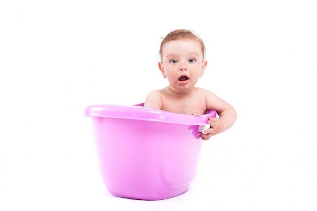 Il piccolo neonato sveglio prende il bagno in vasca porpora