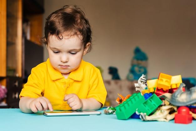 Il piccolo neonato sveglio utilizza lo smartphone a casa al tavolo