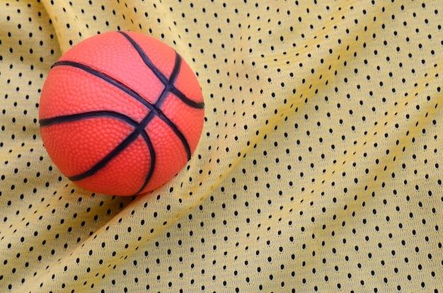 Il piccolo pallacanestro di gomma arancione si trova su una maglia sportiva gialla