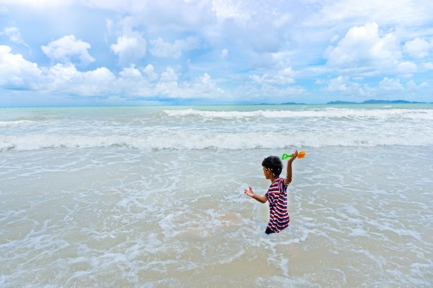 Il piccolo ragazzo asiatico che gioca con la sabbia gioca sulla spiaggia